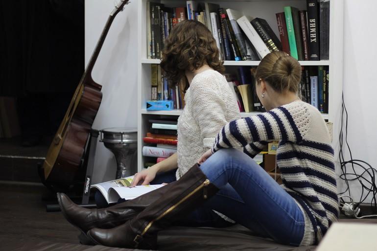 Девушки студентки рядом с книжной полкой