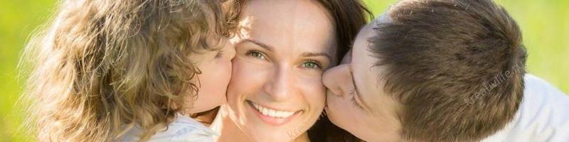 ивая счастливая мама, которую целуют дети