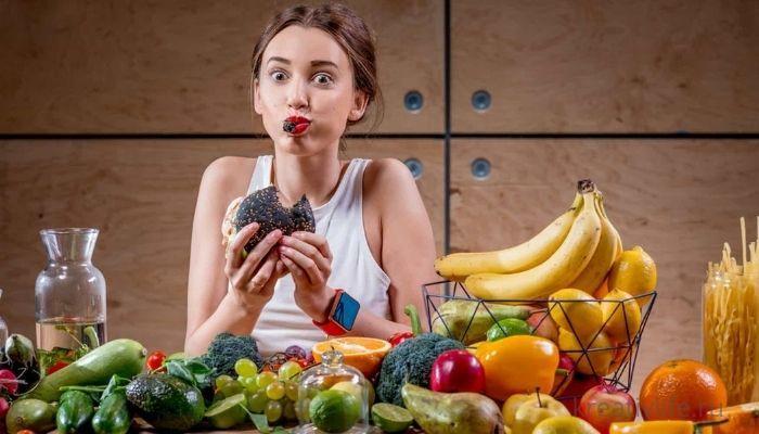Питание, продукты красивые овощи и фрукты кушает девушка