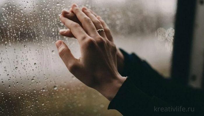 Руки мужчины и женщины на фоне дождя за окном